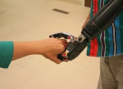 "A user of the DARPA-funded ""Modular Prosthetic Limb,"" in development by a team at the Johns Hopkins Applied Physics Lab, shakes hand with an attendee at the Federal Advanced Amputation Skills Training symposium. (Photo by Randy McCracken)"