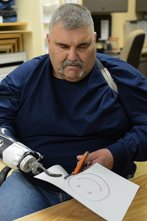 Veteran missing a right hand (hook attached in it's place) is using scissors and doing cratfts